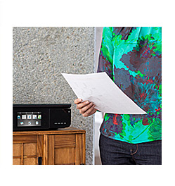 Printer and woman holding document